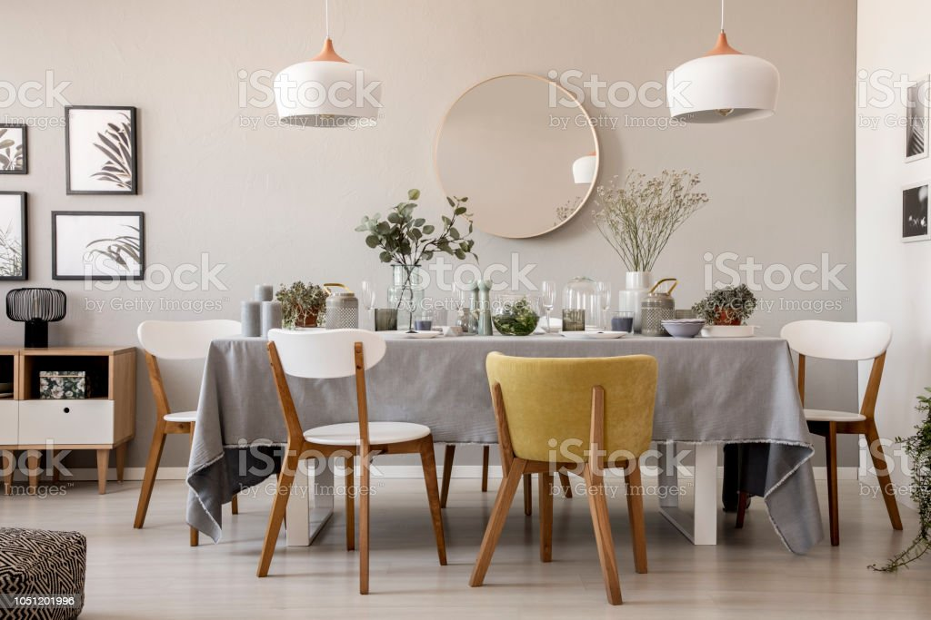 Wooden Chairs At Table With Tableware In Dining Room Interior With Lamps And Round Mirror Real Photo Stock Photo Download Image Now Istock