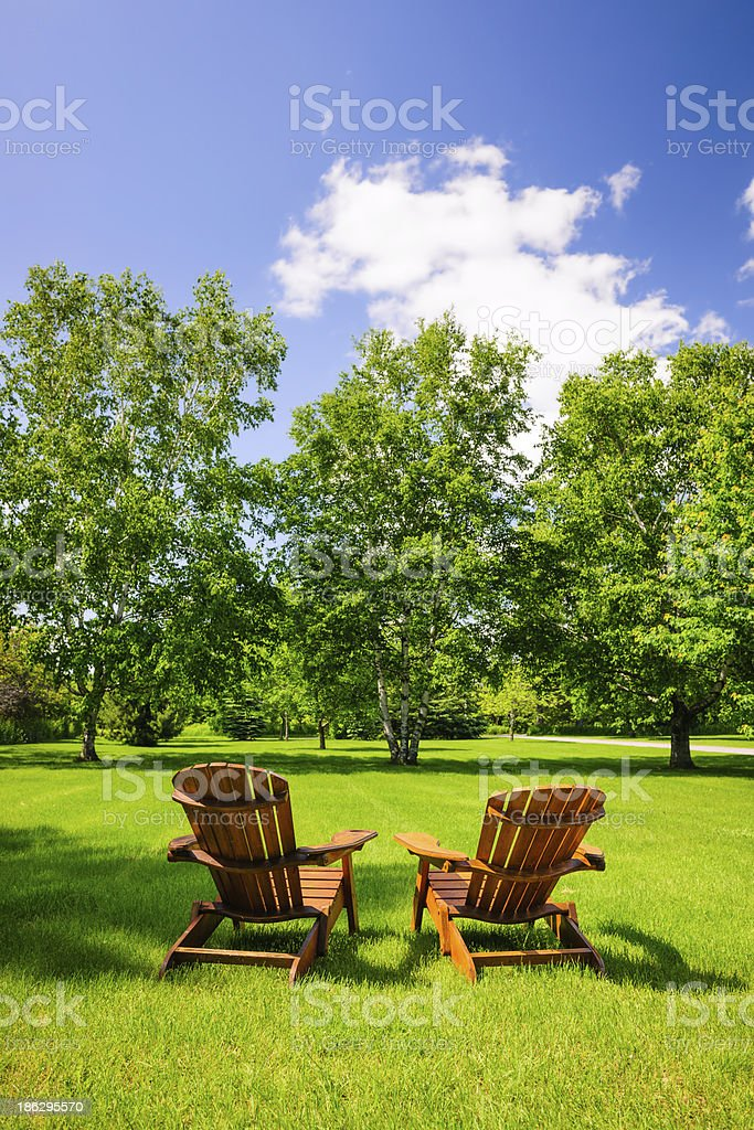 Wooden chairs on a green lawn overlooking some trees stock photo