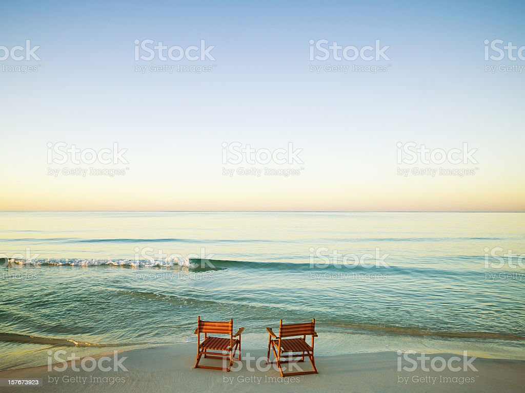 Wooden Chairs on Beach stock photo