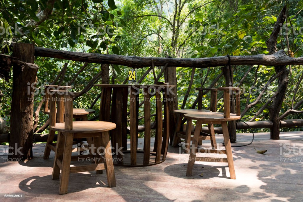 wooden chairs on wood patio of house in forest stock photo
