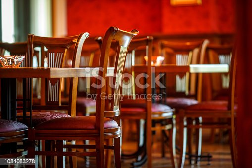 Empty chairs and tables in a food and drink establishment.