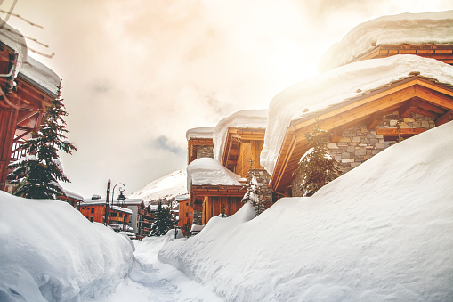 Wooden chalet and snow footpath in french ski resort of Val d'Isere