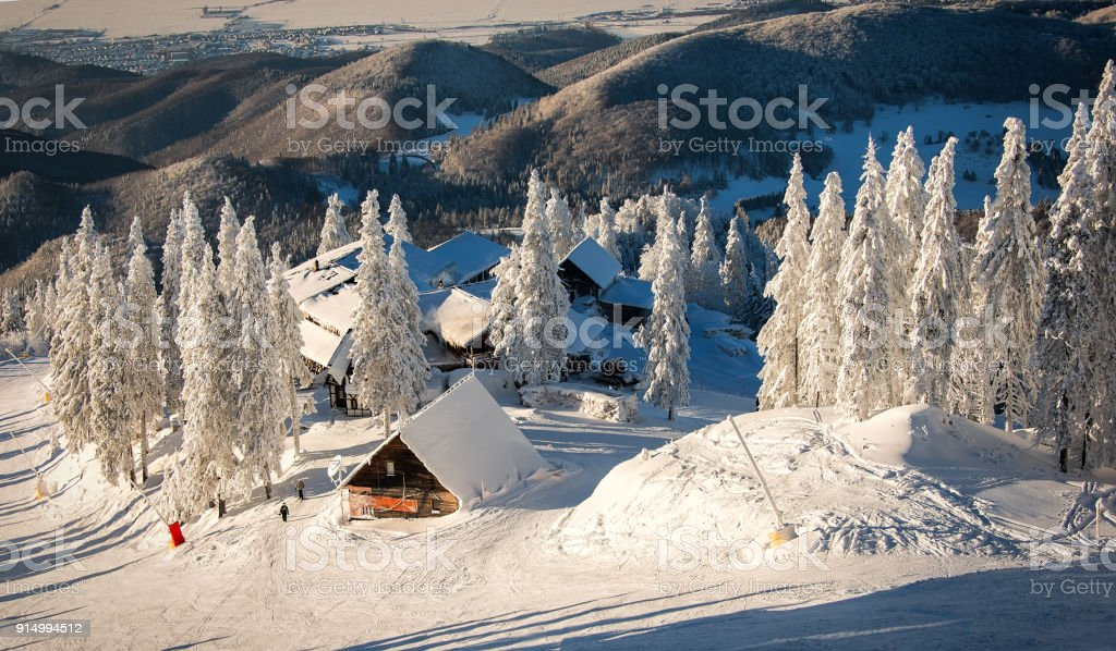 Wooden chalets and spectacular ski slopes in the Carpathians,Poiana Brasov ski resort,Transylvania,Romania,Europe,Pine forest covered in snow on winter season stock photo