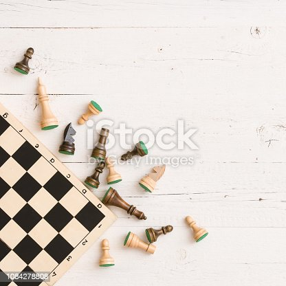 istock Wooden chess figures and chess board on white table background. Top view. 1084278808