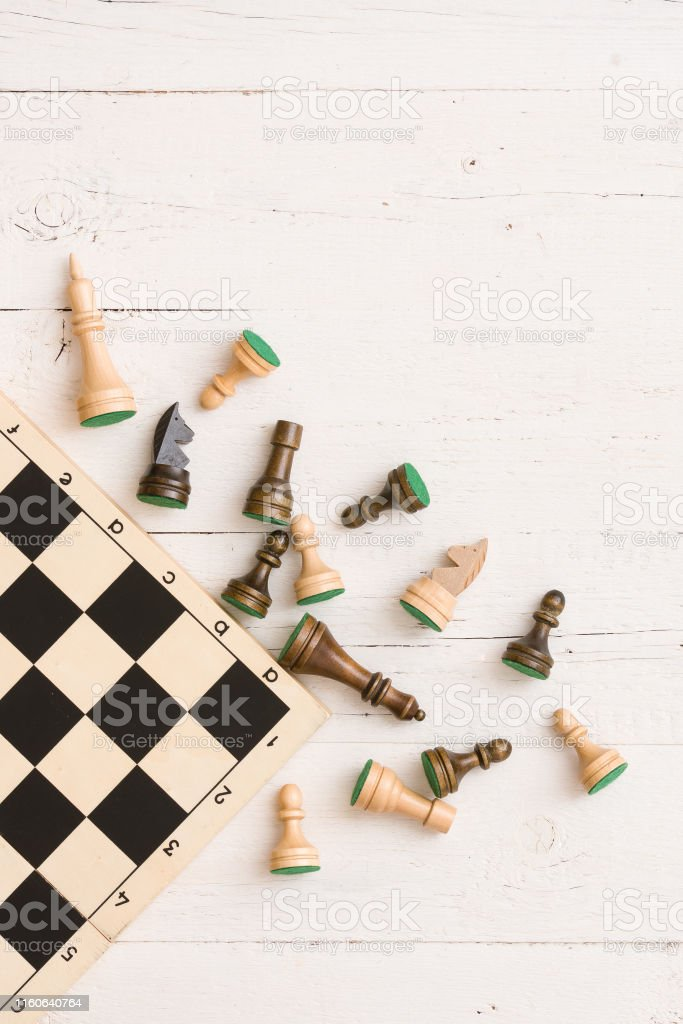 wooden chess figures and part of a chess board on white table...
