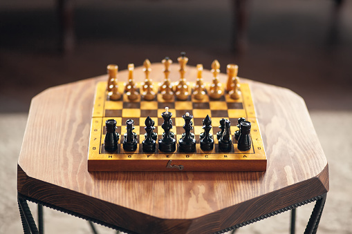 Wooden chess pieces on a board game, on a wooden polygonal vintage table, selective focus.
