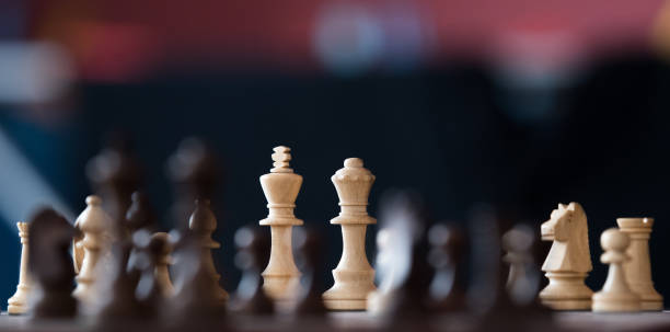 Wooden chess pieces on a chessboards stock photo