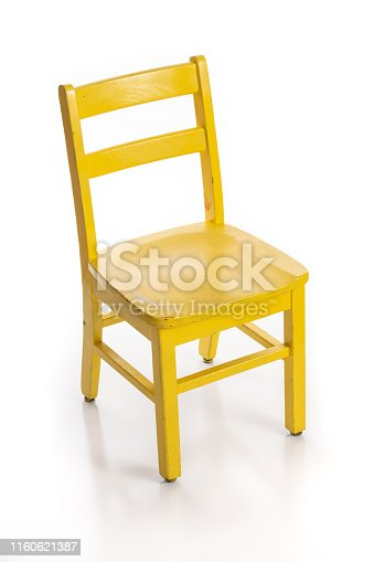 Wooden child chair painted yellow isolated on a white background.