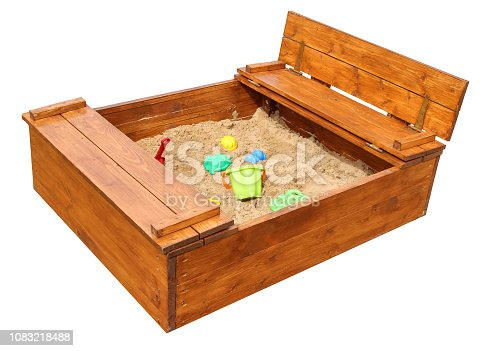 Wooden children sandbox with toys. Isolated on white background