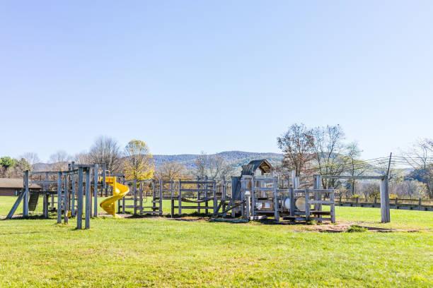 hölzerne kinderspielplatz leer im land von schule mit folie in berglandschaft, ländliche - spielplatz design stock-fotos und bilder
