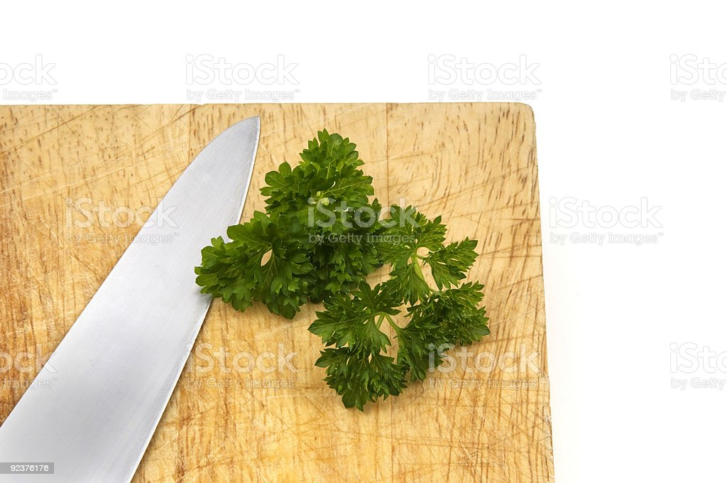Wooden Chopping Board with a Knife and Parsley royalty-free stock photo