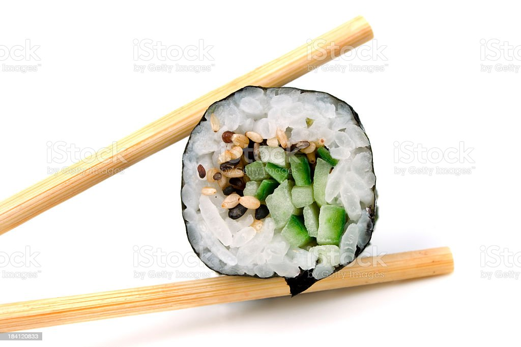 Wooden chopsticks holding vertically a slice of sushi stock photo