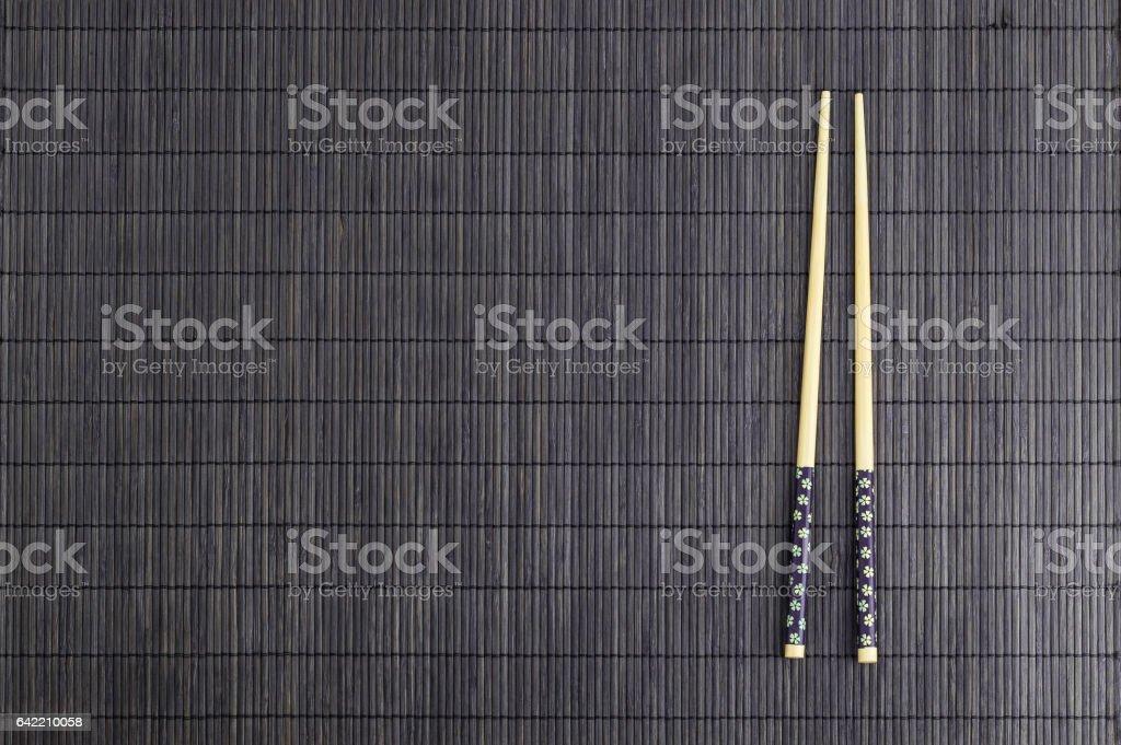 Wooden chopsticks on brown bamboo straw mat stock photo