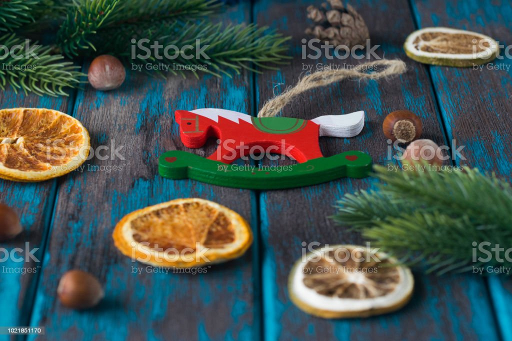 Wooden christmas toy with spruce branches, citrus dried slices, hazelnuts on rustic wooden desk. stock photo