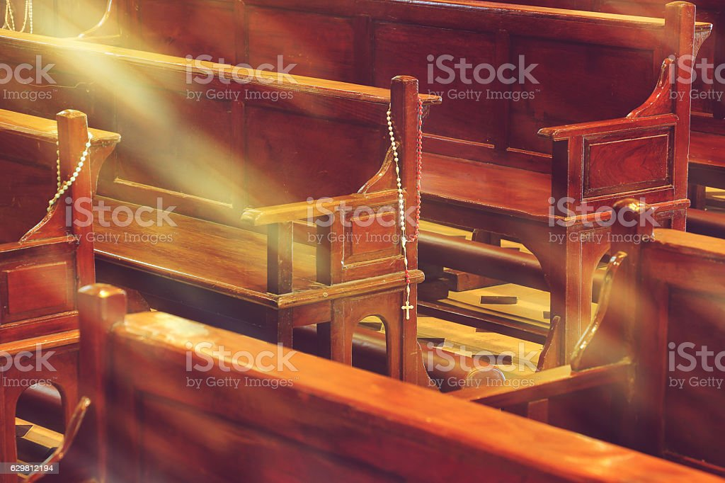 wooden church pews in church and rosary beads with sunlight - foto de acervo