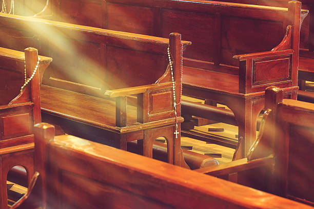 wooden church pews in church and rosary beads with sunlight wooden church pews in church and rosary beads with sunlight pew stock pictures, royalty-free photos & images