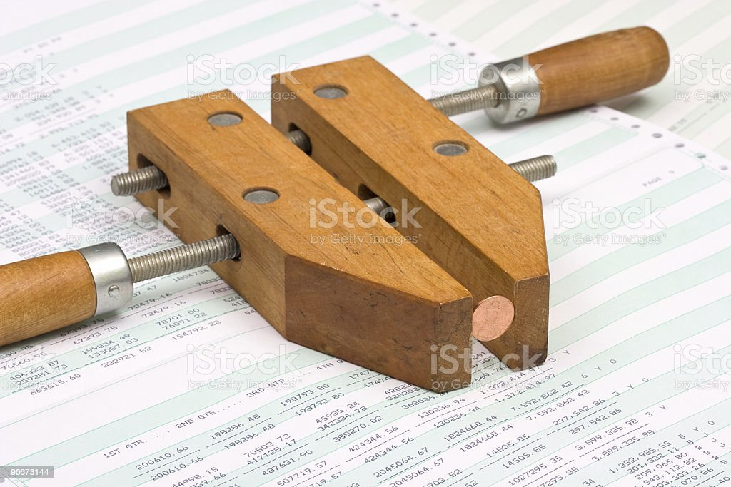 Wooden clamp pinching a penny Know any penny pinching cheapskates?  Or feeling financial pressure?  How about something real for the metaphor?  Well, heres a wooden screw clamp sqeezing the living daylights out of a shiny penny.  The clamp is set on a sales report on green bar paper. Business Stock Photo