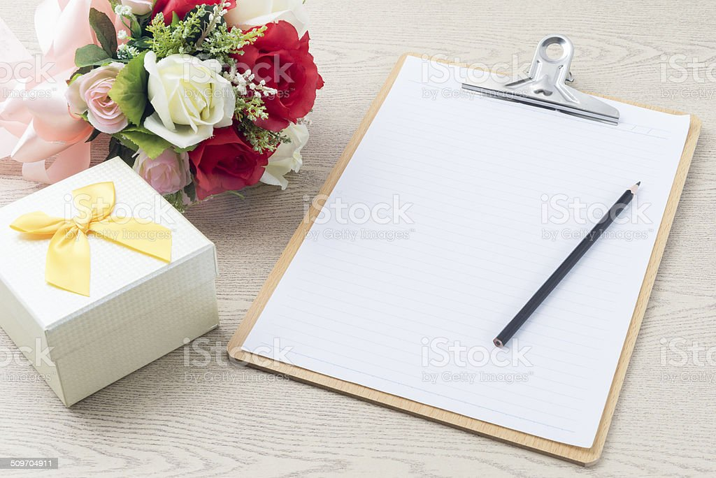 Wooden Clipboard attach planning paper with pencil beside rose b stock photo
