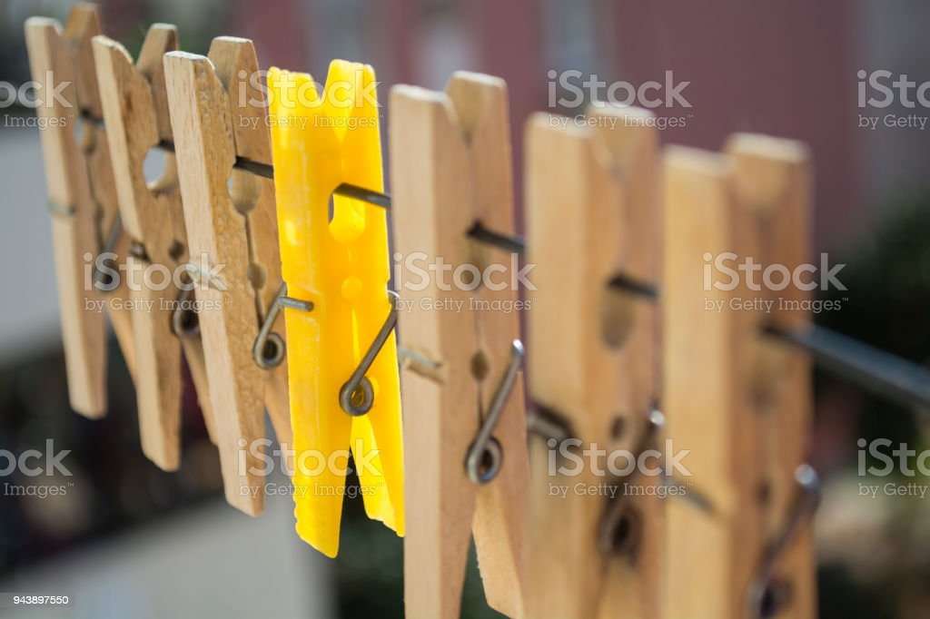 wooden clothespins on a rope and a yellow latch between stock photo