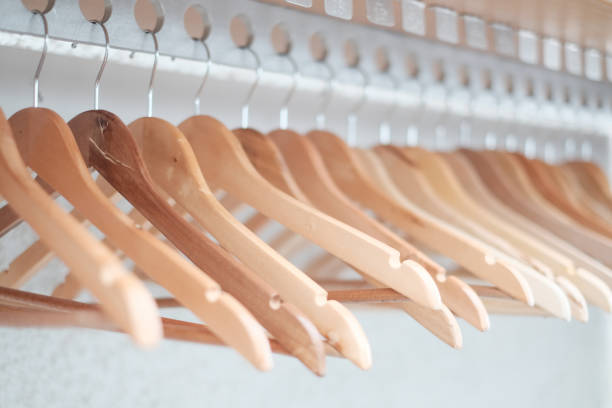 hölzerne kleiderbügel hängend auf einem tuch schiene regal im schrank hotelzimmer. - bügelsysteme stock-fotos und bilder