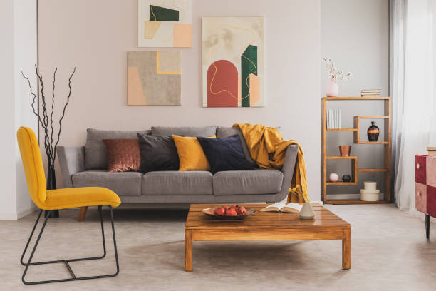 wooden coffee table and yellow chair in front of grey couch with pillows in trendy living room