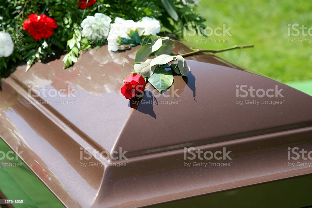 Wooden color casket with flowers and a rose on top stock photo