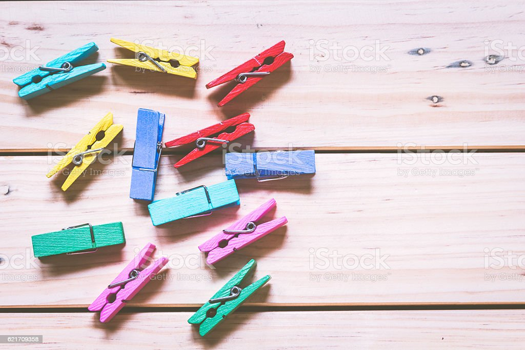 Wooden colored clothespins on wooden background stock photo