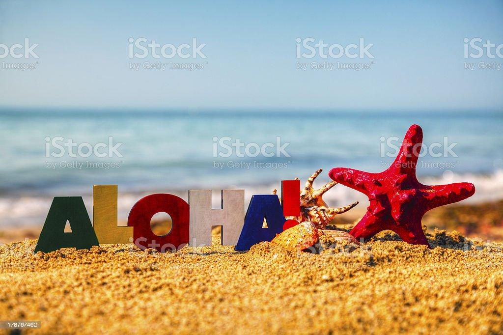 De madera colorida palabra'Aloha'en la arena - foto de stock