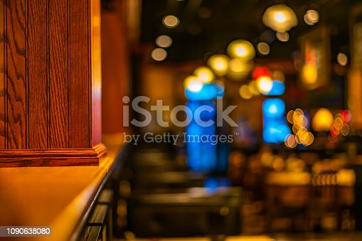 Wooden column dividing the bar/ restaurant area with blurred out surroundings and warm lights with bokeh.