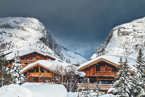 Wooden common chalet in french Val d'Isere ski resort with snowcapped Alps mountain