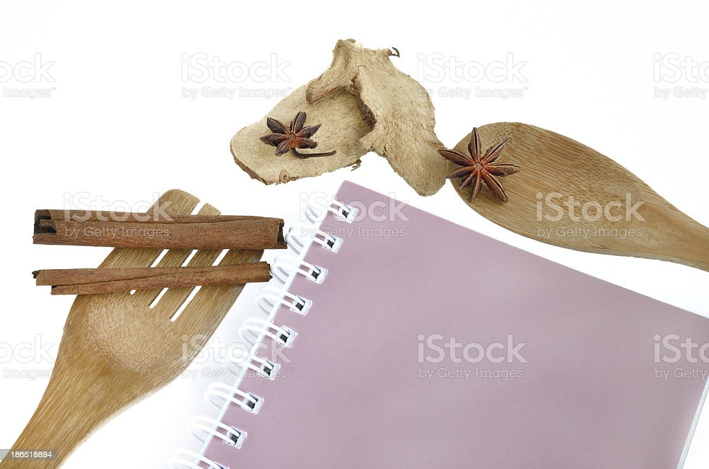 Wooden cooking utensils with book and spices isolated on white royalty-free stock photo