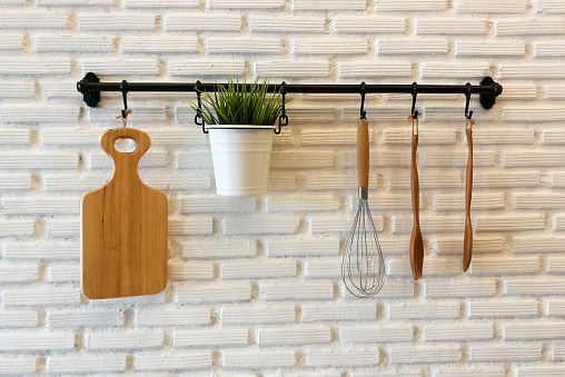 Wooden cookware and plant on flower pot hanging on white brick wall