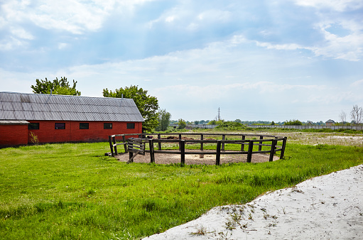 Wooden corral for horse dressage against a blue sky on a sunny day. Grass paddock on farmland with wooden fence. Rural view meadow and fenced place for walking horse
