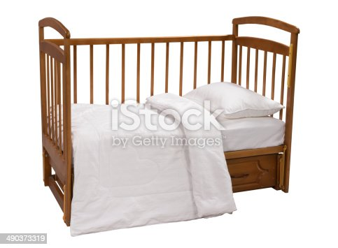 istock Wooden cot with bedding isolated on white background 490373319