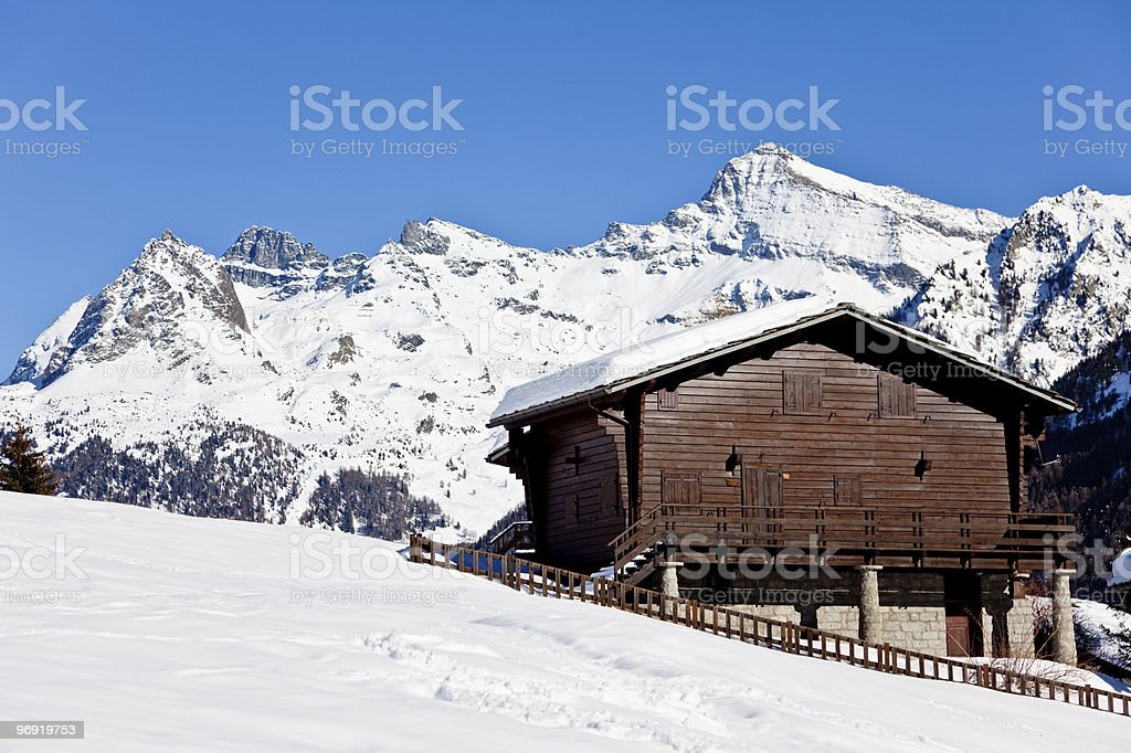 Wooden cottage over snowed mountain royalty-free stock photo
