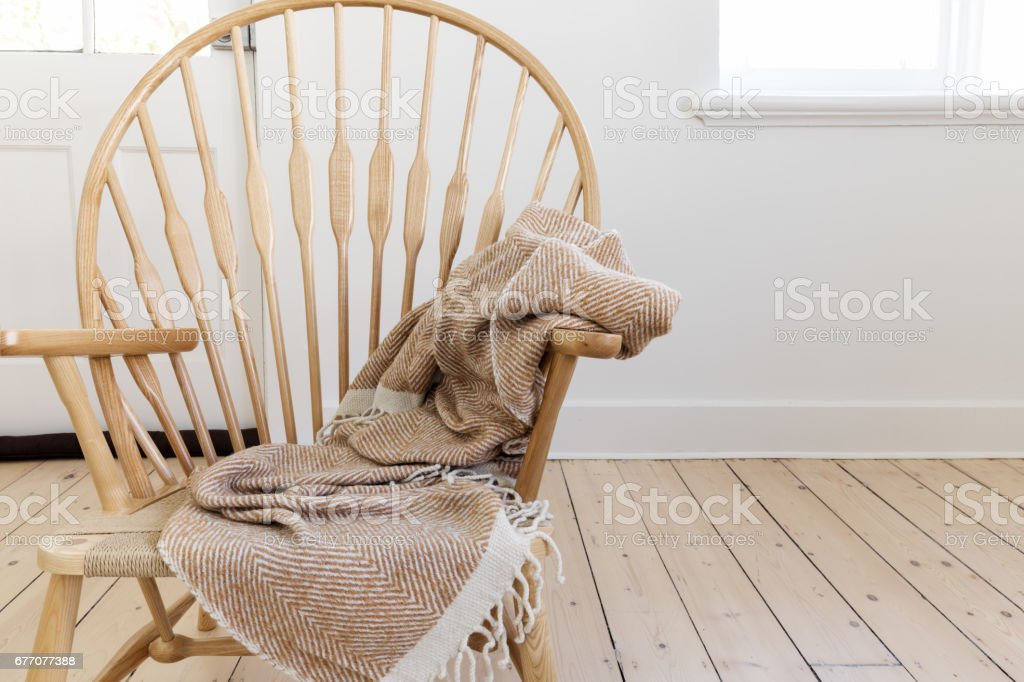 Wooden country style chair with textured throw blanket stock photo