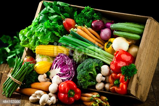 A wooden crate is filled with fresh, colorful organic vegetables. The crate is tilted and some vegetables are out of it on a rustic wood table.  DSRL studio photo taken with Canon EOS 5D Mk II and Canon EF 70-200mm f/2.8L IS II USM Telephoto Zoom Lens