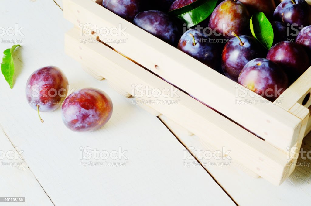 Wooden crate with plums stock photo