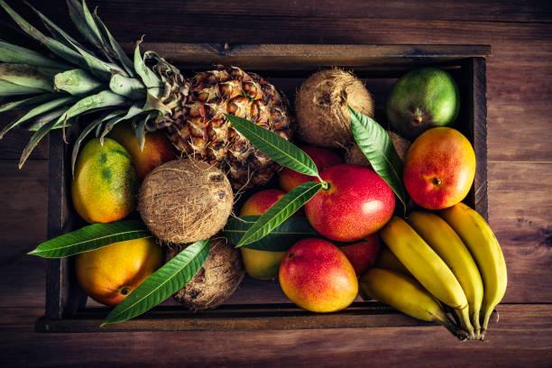 ahşap kasa rustik mutfakta çeşitli tropikal meyve ile. doğal aydınlatma - hindistan cevizi tropik meyve stok fotoğraflar ve resimler
