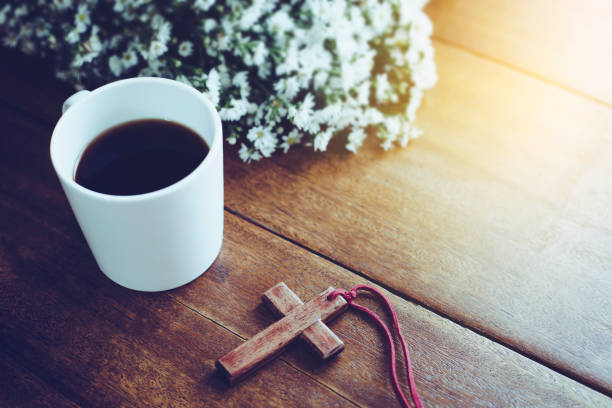 wooden cross and coffee cup the wooden cross  and a cup of cross on wooden table with flower  against 'window light, Christian background with copy space clergy stock pictures, royalty-free photos & images