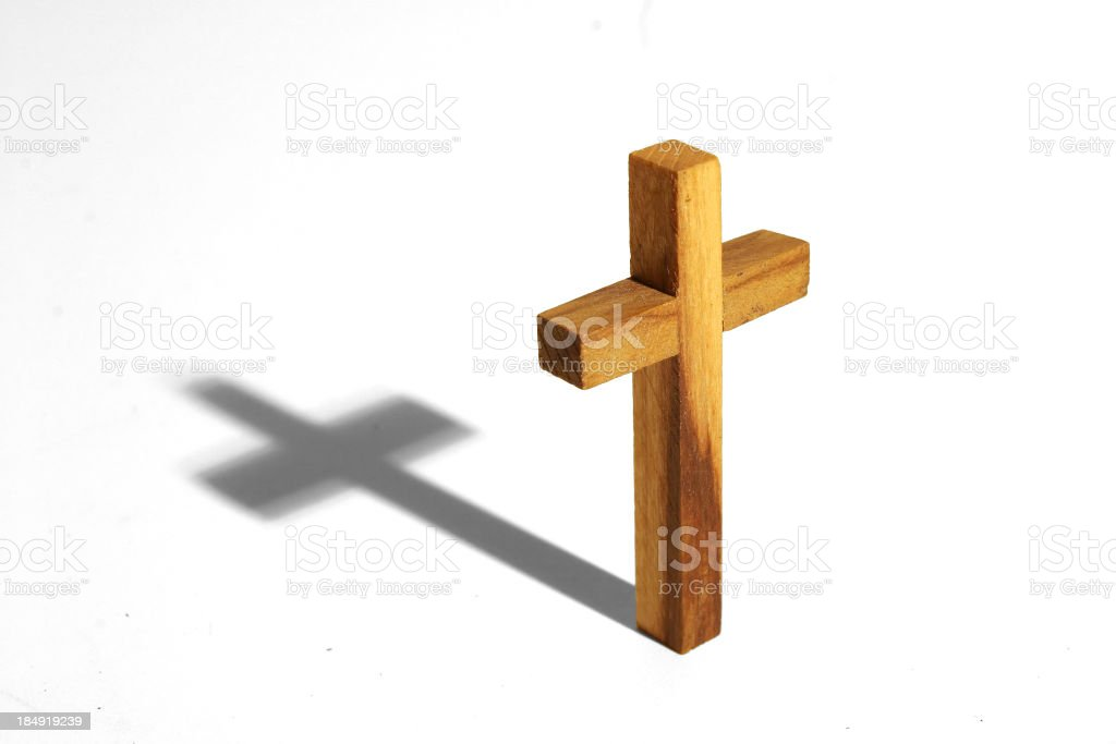 Wooden cross and it's shadow on a white background royalty-free stock photo
