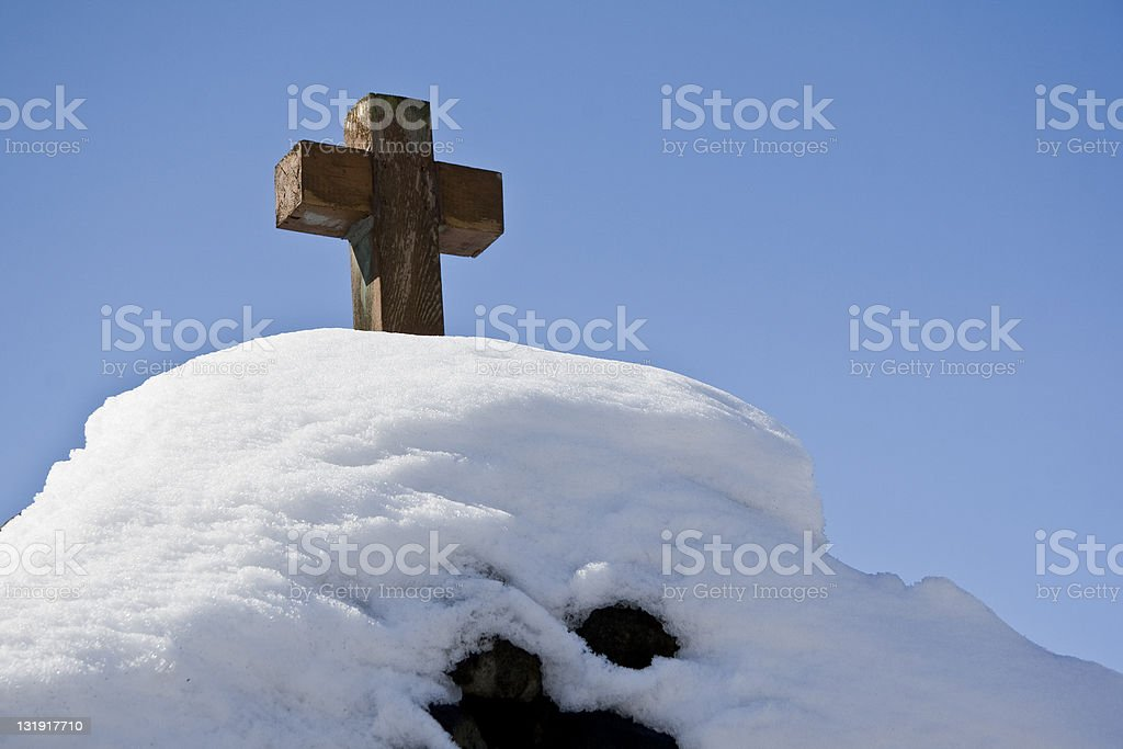 Wooden Cross Atop a Snowy Hill stock photo