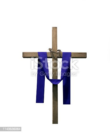 Wood cross draped with purple fabric and thorns isolated against white background.