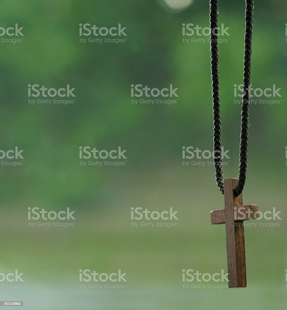 Wooden cross hanging on a black rope royalty-free stock photo