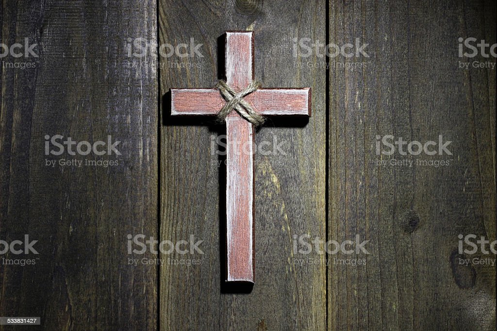 Wooden cross hanging on rustic wood wall stock photo