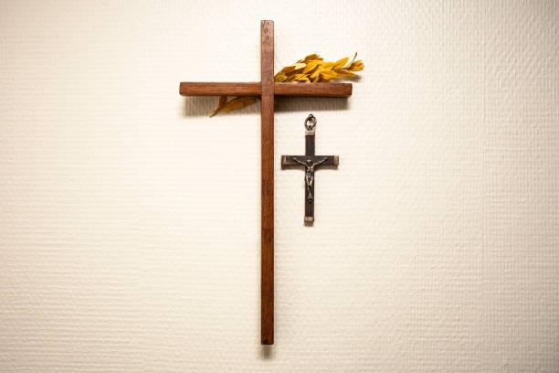 holzkreuz hängt an der wand mit jesus im wohnzimmer, religiöse und spirituelle konzept - achtsamkeit persönlichkeitseigenschaft stock-fotos und bilder