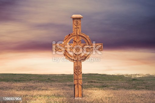 A wooden cross in a beautiful landscape, in the background is the sky with beautiful colors, at sunset