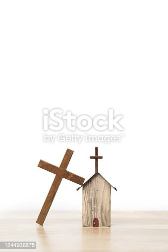 Wooden cross leaning on a small house wooden model on wooden board and white background