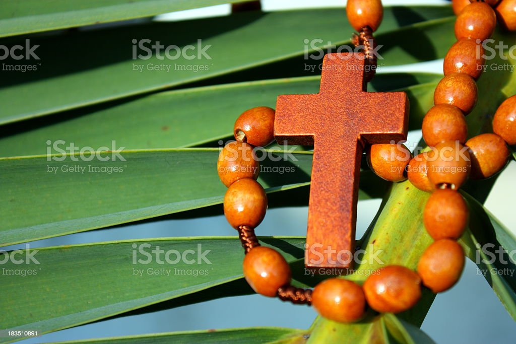 A wooden cross necklace wrapped around a green palm leaf stock photo