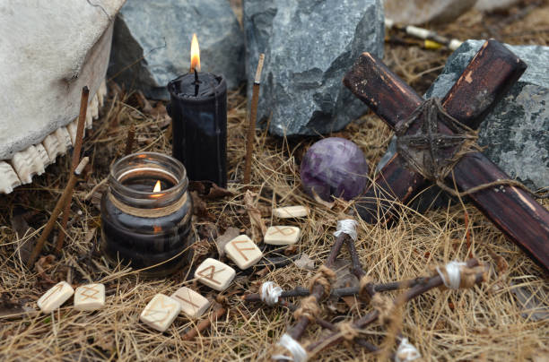 Wooden cross, old runes, pentagram and black candles stock photo